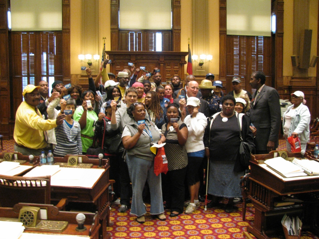 Crowd of people hold MARTA Breeze cards in center of Georgia State House